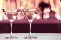 2 cocktail glazen met op de achtergrond lichtjes