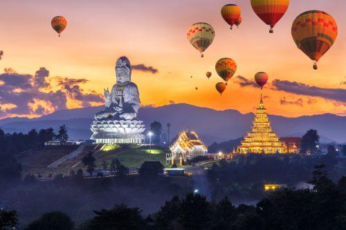 Manifesteer geld met behulp van je gidsen. Buddha beeld met luchtballonnen.